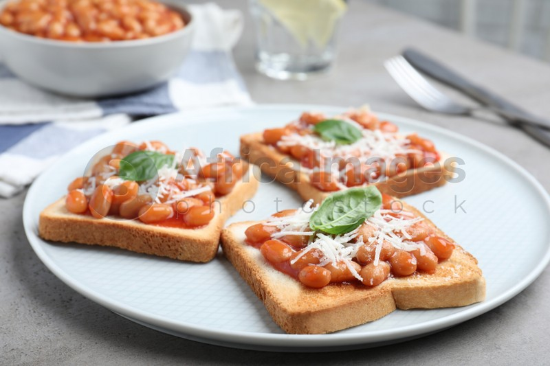 Toasts with delicious canned beans on light grey table