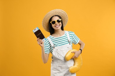 Happy female tourist with ticket, passport and travel pillow on yellow background