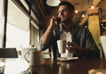 Handsome man with cup of coffee talking on smartphone at cafe in morning