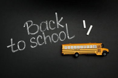 """Yellow bus and phrase """"Back to school"""" on chalkboard, top view. Transport for students"""
