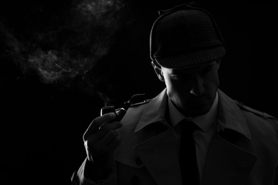 Old fashioned detective smoking pipe on dark background, black and white effect