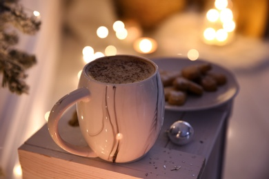 Cup of tasty hot drink and cookies indoors, closeup. Christmas atmosphere
