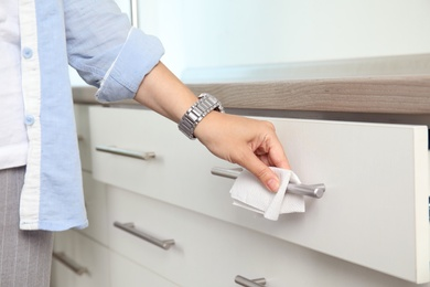 Woman using tissue paper to open drawer, closeup