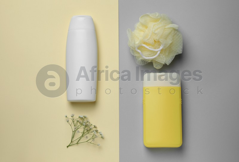 Bottles of shower gel, mesh pouf and flowers on color background, flat lay