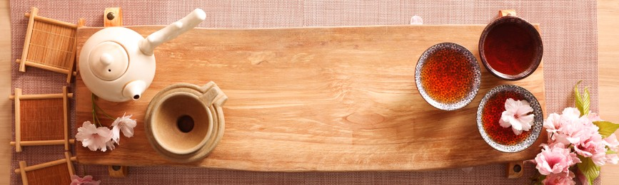 Beautiful set for traditional tea ceremony on wooden table, flat lay. Banner design