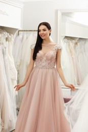 Woman trying on beautiful wedding dress in boutique