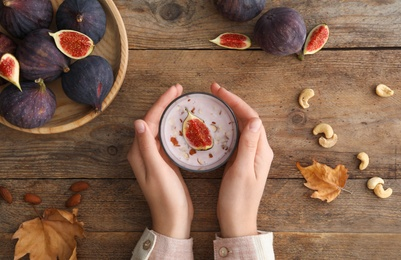 Woman with delicious fig smoothie at wooden table, top view