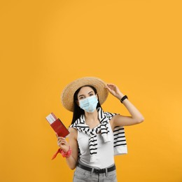 Female tourist in medical mask with ticket and passport on yellow background. Travelling during coronavirus pandemic