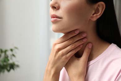Young woman doing thyroid self examination indoors, closeup. Space for text
