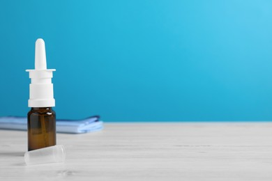 Nasal spray on white wooden table against light blue background. Space for text