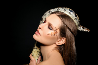 Beautiful woman with boa constrictor on black background
