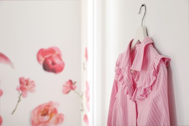 Pink shirt hanging on wall indoors. Space for text