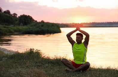 Man meditating near river at sunset. Space for text