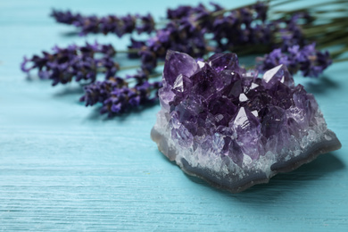Amethyst and healing herbs on light blue wooden table, closeup