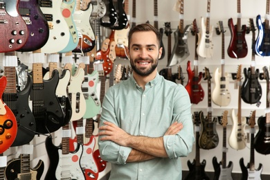 Young shop assistant near guitars in music store