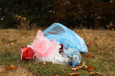 Pile of plastic garbage on grass near forest