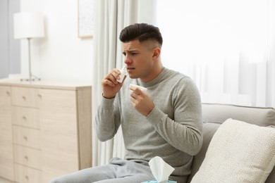 Ill man with paper tissue using nasal spray at home