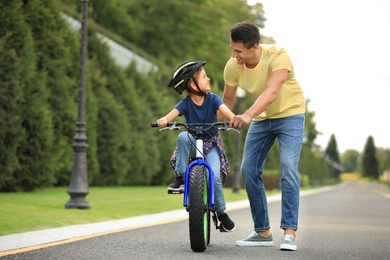Dad teaching son to ride bicycle outdoors