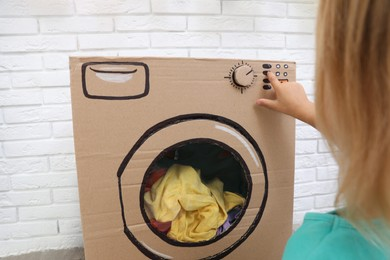 Little girl playing with toy cardboard washing machine indoors, closeup