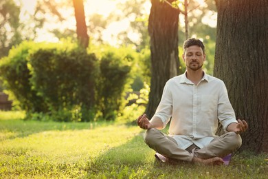 Man meditating in park on sunny summer day. Space for text