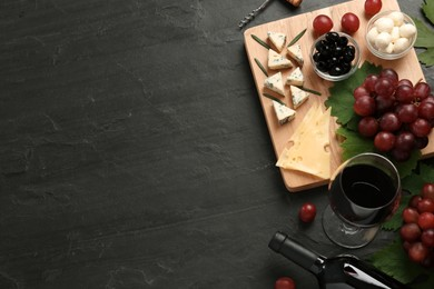 Tasty red wine and snacks on black table, flat lay. Space for text