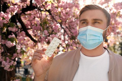 Man with pills and protective mask near blossoming tree outdoors. Seasonal pollen allergy