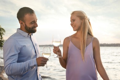 Couple with glasses near river at summer party