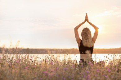 Young woman meditating near river on sunny day, back view. Space for text