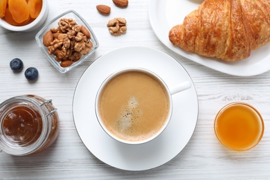 Delicious breakfast with cup of coffee on white wooden table, flat lay