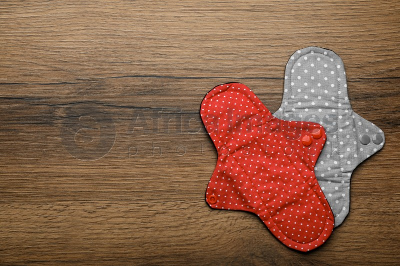 Reusable cloth menstrual pads on wooden table, flat lay. Space for text