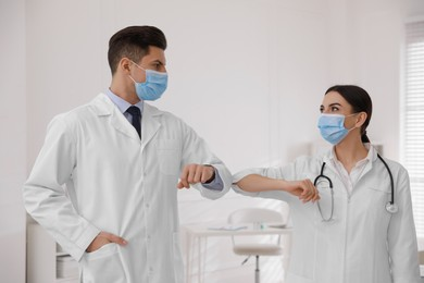 Doctors with protective masks greeting each other by bumping elbows instead of handshake in clinic