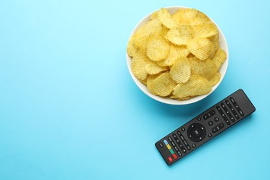 Remote control and bowl of potato chips on light blue background, flat lay. Space for text