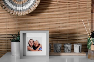 Frame with photo of elderly woman and her granddaughter on white table indoors