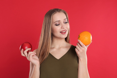 Young woman with apple and orange on red background. Vitamin rich food