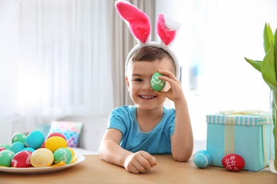 Cute little boy with bunny ears headband playing with painted Easter egg in room