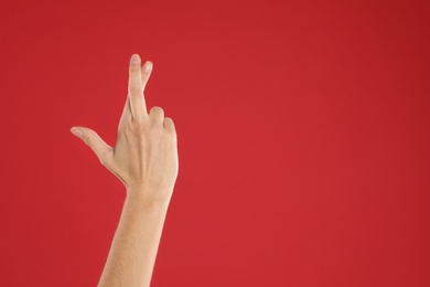 Woman with crossed fingers and space for text on red background, closeup. Superstition concept