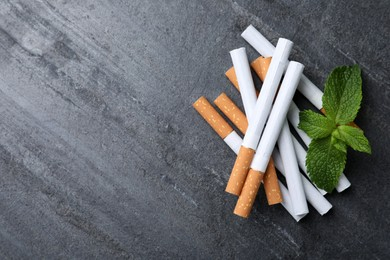 Menthol cigarettes and mint on grey table, flat lay. Space for text