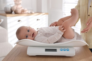 Young woman weighting her cute baby at home, closeup. Health care