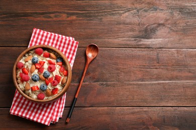 Tasty oatmeal porridge with berries and almond nuts served on wooden table, flat lay. Space for text