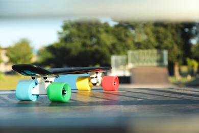 Modern black skateboard with colorful wheels on top of ramp outdoors, space for text