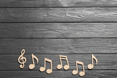 Music notes and treble clef on wooden background, top view. Space for text