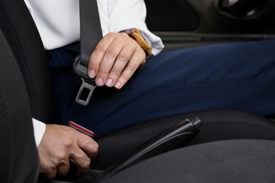 Woman fastening safety belt on driver's seat in car, closeup