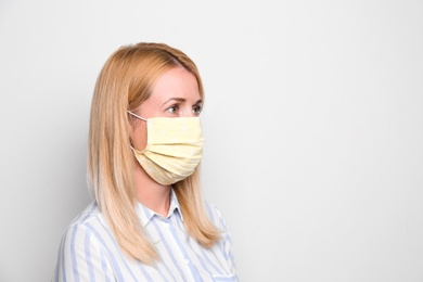 Woman wearing handmade cloth mask on white background, space for text. Personal protective equipment during COVID-19 pandemic
