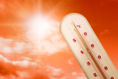 Weather thermometer with high temperature and beautiful sky toned in red on background, space for text