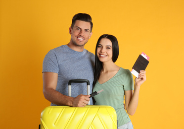 Happy couple with suitcase and tickets in passports for summer trip on yellow background. Vacation travel