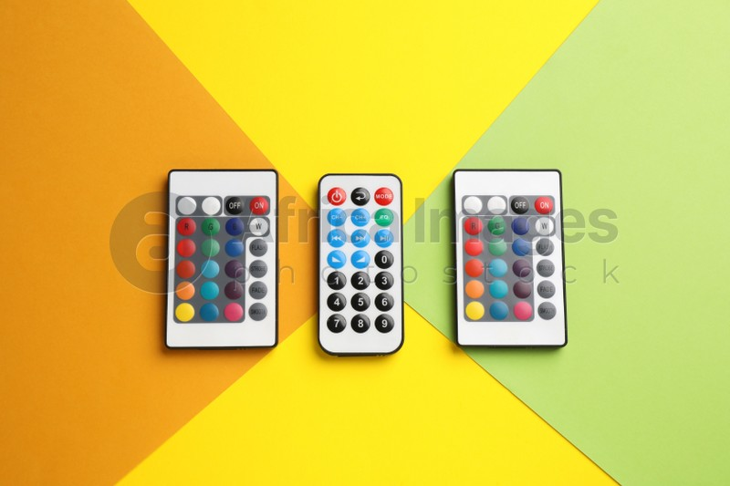 Different remote controls on color background, flat lay