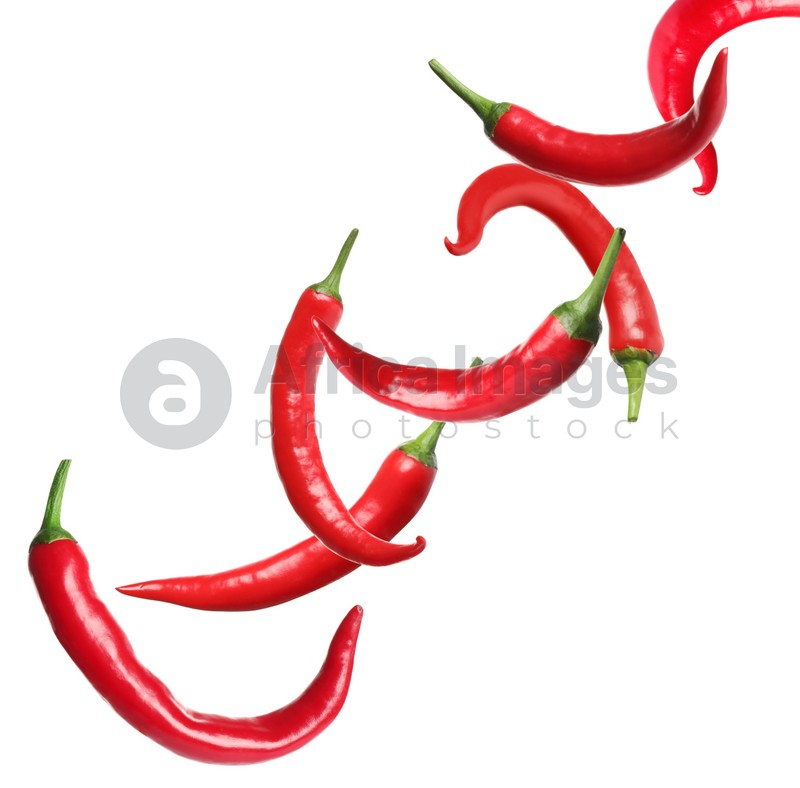 Ripe red chili peppers flying on white background