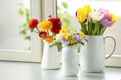 Different beautiful spring flowers on window sill