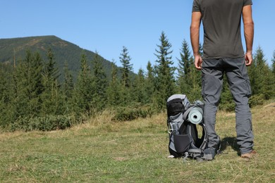 Man with backpack and sleeping mat in mountains, closeup. Space for text