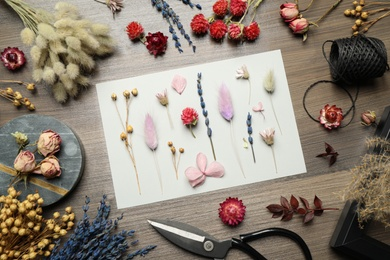 Flat lay composition with beautiful dry flowers on wooden background